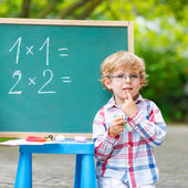 Cute little kid boy with glasses at blackboard practicing mathem — Stock Photo
