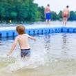 Little blond kid boy having fun with splashing in a lake, outdoo — Stock Photo #81997268