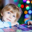 Little blond child playing with cars and toys at home — Stock Photo #81998980