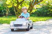 Little boy driving big toy old car, outdoors — Stock Photo