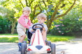 Two little sibling boys playing with pedal car in home's garden — Stock Photo