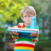 Little school boy with books, apple and drink bottle — Stock Photo