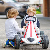 Two happy sibling boys playing with toy car — Stock Photo