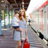 Cute little girl and mother on a railway station. — Stock Photo