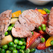 Colorful roast red and yellow bell pepper, green pears, courgette, eggplant and grilled steak with sauce on a plate — Stock Photo #56748339