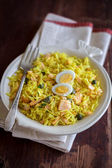 Traditional Scottish dish Kedgeree with basmati rice, curry powder, hot smoked salmon, capers served with hard boiled eggs in a plate for breakfast, selective focus — Stock Photo