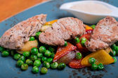 Roasted pork meat fillet chops with zucchini, onion, bell pepper, frozen peas on a plate with cream sauce — Stock Photo