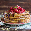 Stack of wheat golden pancakes or pancake cake with freshly picked raspberry, chopped pistachios, chocolate sauce on a dessert plate — Stock Photo #62602053