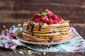 Stack of wheat golden pancakes or pancake cake with freshly picked raspberry, chopped pistachios, chocolate sauce on a dessert plate — Stock Photo