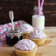Homemade cupcakes with jam, cream frosting with coconut and a bottle of fresh milk on a wooden table, selective focus — Stock Photo #62620759