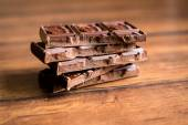 Stack of dark chocolate on a wooden table, selective focus — Stock Photo