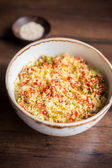 Couscous with green and red bell pepper, olive oil and sesame seeds in a bowl, selective focus — Stock Photo