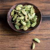 Green aromatic cardamom in a wooden bowl, selective focus — Stock Photo