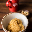 Homemade cookies with ginger, oat flakes and peanut butter in a bowl with a pot of fresh milk for breakfast or snack — Stock Photo #75870341