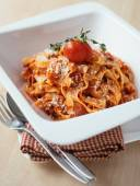 Homemade tagliatelle pasta with bolognese sauce cooked from celery, carrot, minced meat, onion and tomatoes garnished with cherry tomato and freshly grated parmesan cheese — Stock Photo