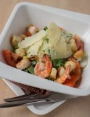 Caesar salad with roasted prawns in a plate on a wooden table, selective focus — Stock Photo
