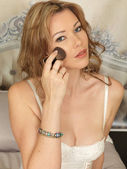 Beautiful Young Woman Posing on a Bed Applying Make Up — Stock Photo