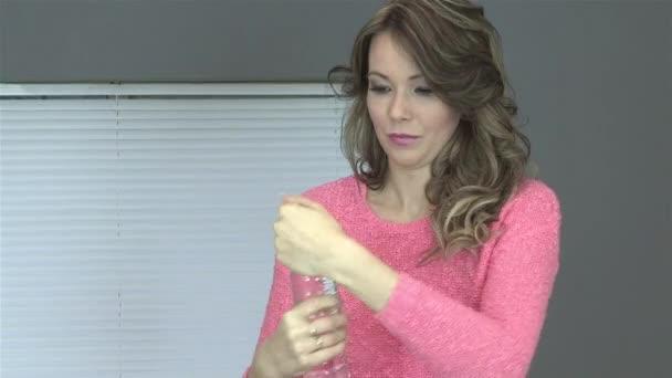 Mujer joven feliz bebiendo una botella de agua — Vídeo de stock