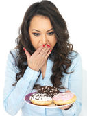 Young Woman Tempted by Iced Donuts — Stock Photo