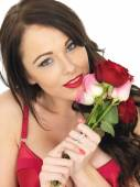Sexy Young Woman Wearing Red Lingerie and Holding Red Roses — Stock Photo