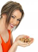 Young Woman Holding a Handful of Mixed Nuts — Stock Photo