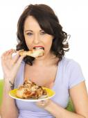 Young Woman Eating Cold Cooked Chicken Legs — Stock Photo