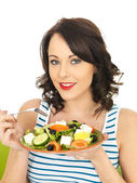 Young Woman Eating a Fresh Crispy Greek Salad — Stock Photo