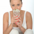 Healthy Attractive Young Woman Holding a Glass of Iced Water wit — Stock Photo #70524707