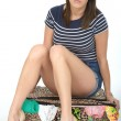 Sad Miserable Upset Young Woman Sitting on a Suitcase packed Full with Holiday Clothes — Stock Photo #71733999