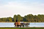 Couple sitting on a bench beside a lake in Groningen, Netherland — Stock Photo