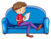 A boy sitting at the sofa with a gadget — Stock Vector
