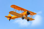 Yellow biplane on the blue sky. — Stock Photo