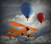 Biplane and hot air balloons — Stock Photo