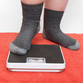 Overweight woman on a retro style weighing machine — Stock Photo