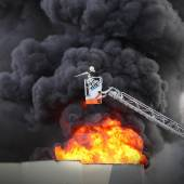 Firefighter and burning house. — Stock Photo