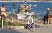 Fishermen mending their nets near  their boats at Tasucu port — Stock Photo