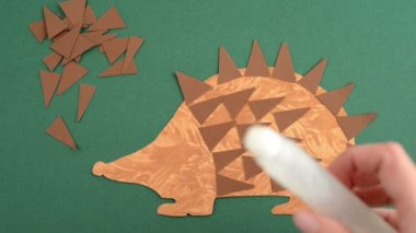 Stuck bristles with glue on hedgehog of paper — Stock Video