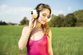 Sexy woman with headphones outside — Stock Photo