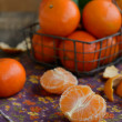 Cloves of tangerines and wire basket full of ripe fruits — Stock Photo #52856961