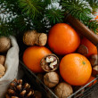 Xmas decoration wih tangerines, nuts and pine tree twigs — Stock Photo #61929591