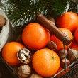 Xmas decoration wih tangerines, nuts and pine tree twigs — Stock Photo #61929625