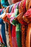 Various colorful scarves hanging at street bazaar — Stock Photo