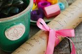 Wrapping paper roll with pink bow and colorful ribbons — Stock Photo
