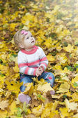 Baby girl with autumn leaves — Stock Photo