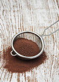 Sieve with cocoa powder — Stock Photo