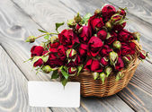 Red roses in basket and greeting card — Stock Photo