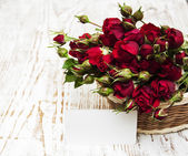 Red roses in basket and greeting card — Stock fotografie