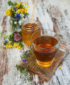Cup of tea, honey and flowers — Stock Photo