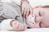 Cute baby girl sleeping over white bedcover — Stok fotoğraf