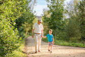 Grandfather and grandchild walking outdoors — Stock Photo